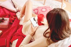 Girl dressed knitted dress and knitted socks lies on red-white blankets and pillows and holds a mobile phone and red cup stock photos