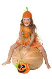 Girl dressed like Cinderellai sits on a pumpkin. Royalty Free Stock Photography