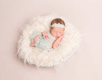 Girl dressed in lovely pastel suit sleeping. Sweet child girl dressed in lovely pastel suit sleeping on a big soft warm pillow Royalty Free Stock Image