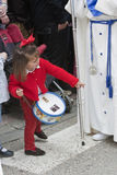 Girl dressed in red with a toy drum looking in front of a Nazarene Royalty Free Stock Images