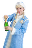 Girl dressed in russian christmas costume. Smiling girl dressed in traditional russian christmas costume of Snegurochka (Snow Maiden) opens bottle of champagne Stock Image