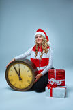 Girl dressed in santa hat with a Christmas Stock Images