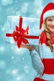 Girl dressed in santa hat with a Christmas gift Royalty Free Stock Images