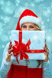 Girl dressed in santa hat with a Christmas gift Stock Image