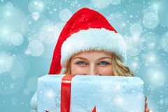 Girl dressed in santa hat with a Christmas gift Stock Photo
