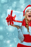 Girl dressed in santa hat with a Christmas gift Stock Photos