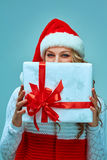 Girl dressed in santa hat with a Christmas gift Royalty Free Stock Image