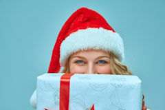 Girl dressed in santa hat with a Christmas gift Stock Photography