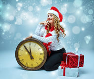 Girl dressed in santa hat holding with a Christmas Stock Images