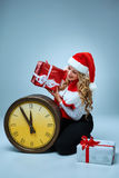 Girl dressed in santa hat holding with a Christmas Stock Photo