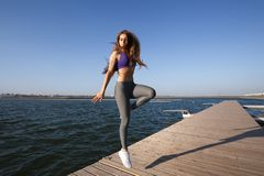 Girl dressed in sports clothes jumping on the wooden pier on a summer day. stock photos