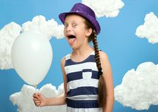Girl dressed in striped dress and color hat posing on a blue background with cotton clouds, white air balloon, the concept of summ Stock Photo