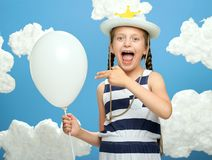 Girl dressed in striped dress and hat with star posing on a blue background with cotton clouds, white air balloon, the concept of. Summer, happiness and holiday stock photography