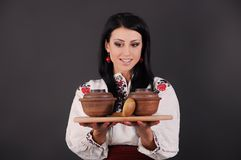 Girl dressed in Ukrainian style, clay utensils. Girl dressed in Ukrainian style and clay utensils royalty free stock photos