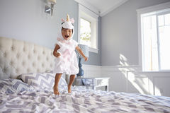 Girl Dressed In Unicorn Costume Jumping On Bed At Home Stock Images