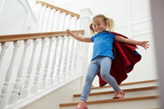 Girl Dressed Up As Superhero Playing Game On Stairs Royalty Free Stock Photography