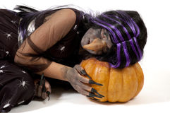 Girl dressed up as a witch sleeping on a pumpkin Stock Images