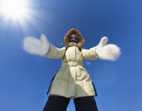 Girl dressed in warm clothes stretches out her hands to you against bright sun. Embracing helping hands. Hands dressed stock photography