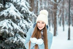 A girl dressed in warm winter clothes and a hat posing in a winter forest. Model with a beautiful smile near the Christmas tree. Stock Photos