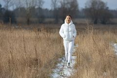 Girl Dressed In White Walks At Countryside. Preety smiling girl dressed all in white walks through the high dry grass field by snowy pathway at winter stock photos