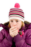 Girl dressed in winterclothes blowing Stock Photo