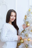 Girl dresses up Christmas tree Royalty Free Stock Photos