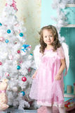 Girl dresses up Christmas tree Stock Photography
