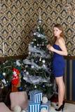Girl dresses up Christmas tree Royalty Free Stock Photography