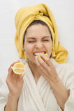 Girl in a dressing gown bites a lemon royalty free stock photos