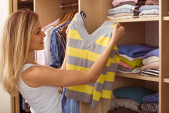 Girl in a dressing room. Beautiful girl is smiling while choosing pullover in her dressing room Stock Photo