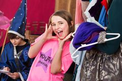 Girl in dressing room poses with hands by face. Girl in dressing room wearing pink shirt places hands by mouth and shouts with glee Royalty Free Stock Photography