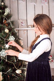 Girl dressing up christmas tree Stock Image