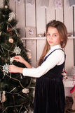 Girl dressing up christmas tree Stock Images