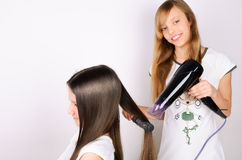 Girl dries hair the hair dryer other teen girl Stock Photography