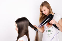 Girl dries hair the hair dryer. Two girls on the light background, horizontal Royalty Free Stock Photos