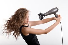 Girl dries long hair with hairdryer Royalty Free Stock Photos