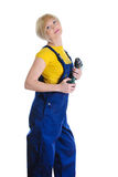 Girl with a drill in building overalls Stock Images