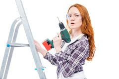Girl with a drill on a stepladder posing on a white. Background Royalty Free Stock Photos