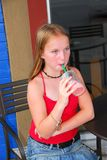 Girl with a drink. Young girl sitting in outside cafe and drinking a cool refreshing beverage on a hot summer day Royalty Free Stock Image