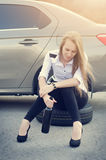 Girl drink a alcohol. Broken car on a background. Woman sit on a wheel.woman repair a car. Natural background. Car accide Stock Photos