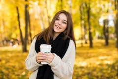 Girl drink coffee in autumn yellow  sunny park Stock Photos