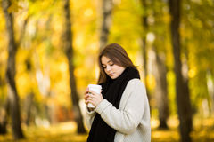 Girl drink coffee in autumn yellow  sunny park Stock Image