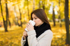 Girl drink coffee in autumn yellow  sunny park Royalty Free Stock Photography