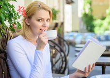 Girl drink coffee while read bestseller book by popular author. Mug coffee and interesting book best combination perfect. Weekend. Woman have drink cafe terrace stock photos