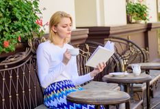 Girl drink coffee while read bestseller book by popular author. Reading is her hobby. Mug coffee and interesting book. Best combination perfect weekend. Woman royalty free stock image