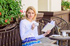 Girl drink coffee while read bestseller book by popular author. Woman have drink cafe terrace outdoors. Reading is her. Hobby. Mug coffee and interesting book stock photography