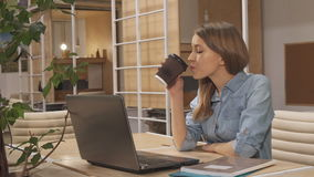 Girl drink coffee at the working hub. Pretty brown haired girl drinking coffee at the working hub. Cute young woman having a break at her workplace. Attractive stock footage