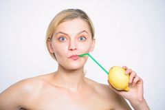 Girl drink fresh juice whole lemon fruit with cocktail straw. Benefits of drinking lemon water in morning empty stomach. Lemonade vitamin beverage. Healthy royalty free stock photo