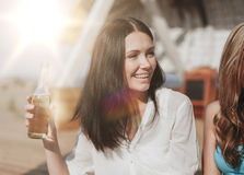 Girl with drink and friends on the beach Stock Images