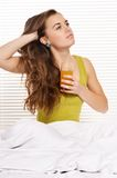 Girl drink juice in bed Stock Images
